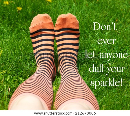 Inspirational quote about individuality by an unknown author with a teenaged girl's legs with crazy socks laying on the grass in summer. - stock photo