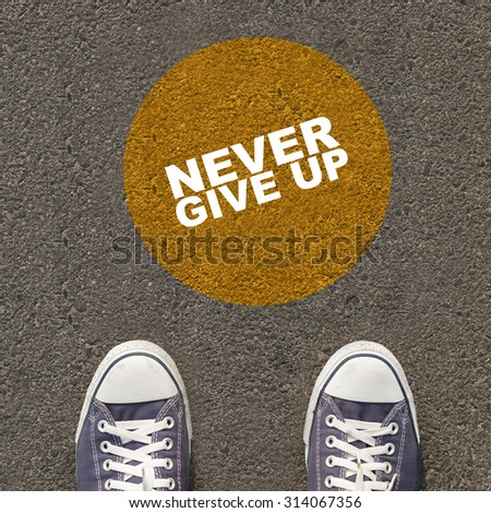 Inspirational Typographic Quote on yellow circle : pair of shoes on the asphalt road. - stock photo