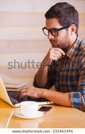 Inspire with cup of fresh coffee. Confident young man working on laptop while sitting in coffee shop - stock photo