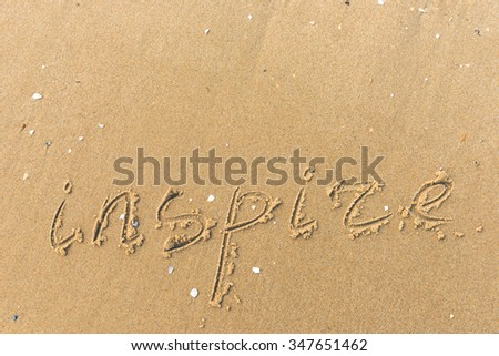 Inspire written on the beach. sand background - stock photo