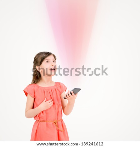 Inspired cute little girl in red dress looking up on ray of light from mobile phone in her hand. Isolated on beige background. - stock photo