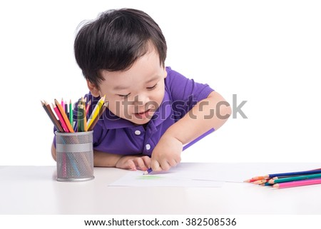 Inspired little boy at the table draw with crayons, isolated on white. Asian Boy, drawing a picture for fathers day - stock photo