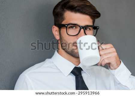 Inspired with cup of fresh coffee. Confident young man in shirt and tie drinking coffee and looking away while standing against grey background - stock photo