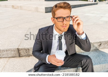 Inspired with cup of fresh coffee. Top view of thoughtful young man in formalwear holding coffee cup and adjusting his eyeglasses while sitting outdoors - stock photo