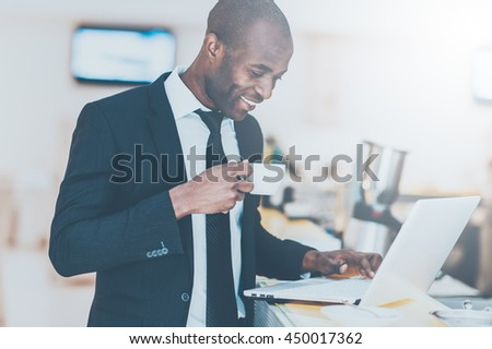 Inspired with fresh coffee. Cheerful young African man in formalwear using his laptop while standing at the bar - stock photo