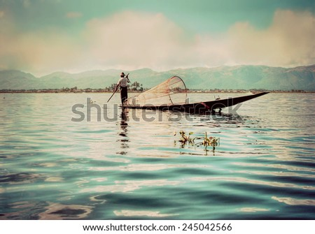 Instagram filter look silhouette of a traditional fishersboat on the Inle lake in Myanmar . .   - stock photo