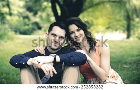 Instagram look of an image showing a happy young couple sitting on the ground in a garden setting after becoming engaged. - stock photo