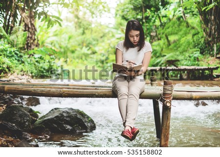 Instagram looking image of Woman sitting at the wood bridge ,writing in the notebook.