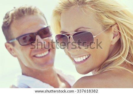 Instagram style photograph of happy and attractive man and woman couple wearing sunglasses and smiling in sunshine at the beach - stock photo