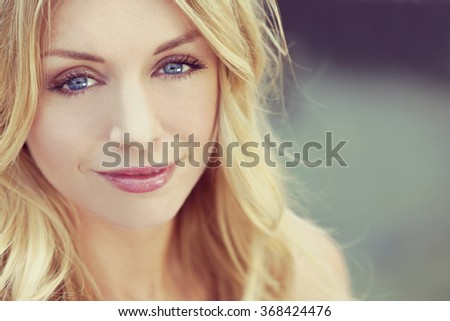 Instagram style portrait of naturally beautiful woman in her twenties with blond hair and blue eyes, shot outside in natural sunlight - stock photo