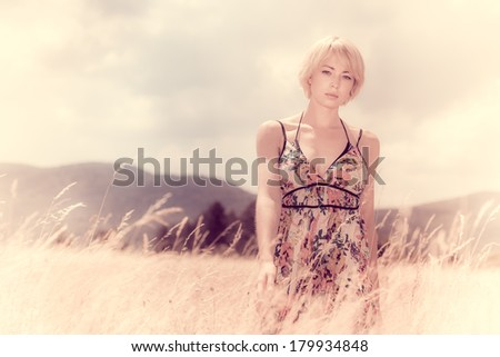 Instagram style retro summer shot of a lady in the meadow.