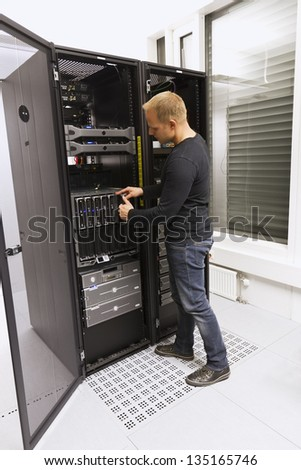 Install or remove a blade server in a blade chassis in a rack. Shot in a data center. - stock photo