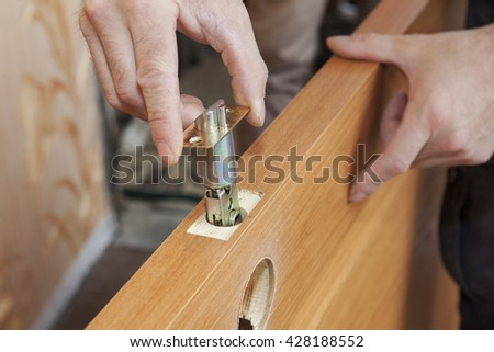 Installation locked interior door knobs, close-up woodworker hands install lock. - stock photo