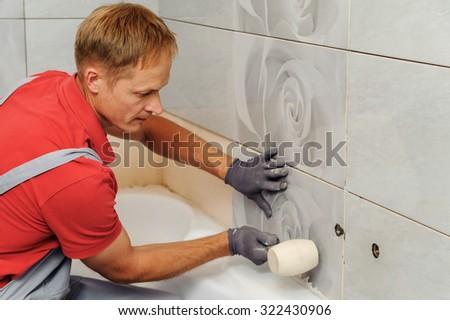 Installation of  ceramic tiles. Tiler knocks a rubber mallet - stock photo
