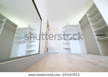 Installation of white corner sliding wardrobe and its reflection in mirror - stock photo