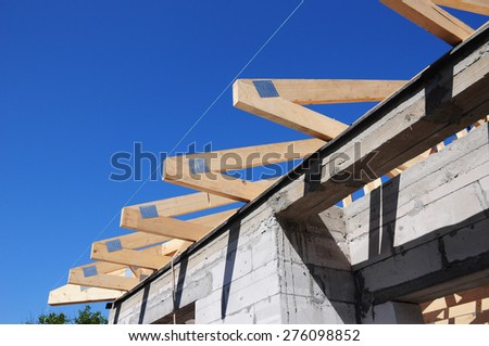 Installation of wooden beams at construction the roof truss system of the  house - stock photo