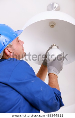 Installing a new light bulb - stock photo