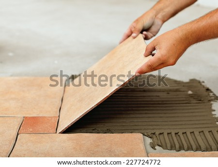 Installing ceramic floor tiles - placing the tile into the adhesive material bedding, closeup - stock photo