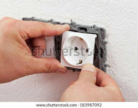 Installing electrical outlet or socket - closeup on electrician hands - stock photo