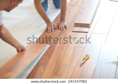 Installing laminate flooring in new home indoor - stock photo