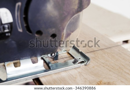 Installing laminate flooring. Worker cut part of the board with an electric jigsaw - stock photo