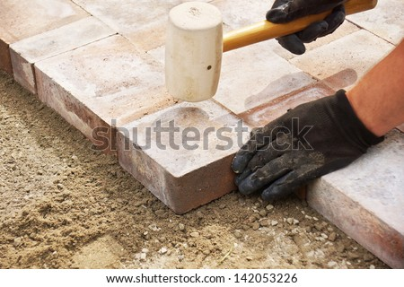 Installing paver bricks on patio, mallet to level the stones