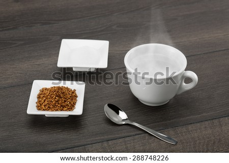 Instant coffee granules and sugar ready for the hot water. On dark wooden table. - stock photo