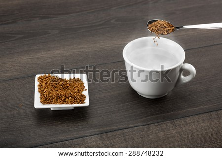 Instant coffee granules poured from a table teaspoon into hot steamy water. Shallow depth of field. - stock photo