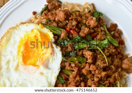 instant noodle topping spicy stir fried chop pork and basil leaf with egg