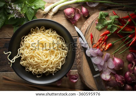 Instant noodles in white black on wood background, Top view, Asian meal on a table, junk food concept