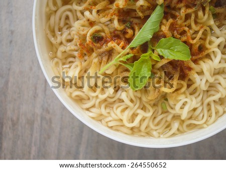 Instant noodles in white dish on old table background - stock photo