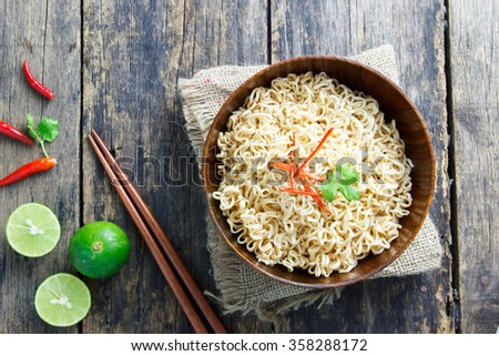 Instant noodles in wooden bowl on wood background  - stock photo