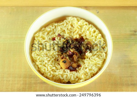Instant noodles in yellow dish on wood background - stock photo