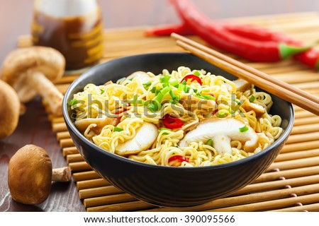 Instant noodles with shiitake mushrooms, pepper and onion in a bowl, Asian meal on a table - stock photo