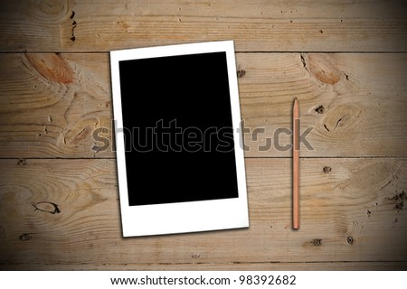 Instant photo and a pencil on a wooden table - stock photo