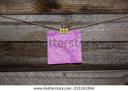 Instant photo and paper heart hanging on the clothesline without words on old wood background