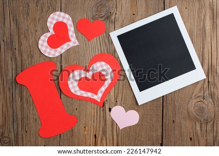 Instant photo and paper letter with hearts forming phrase I LOVE on old wooden background - stock photo