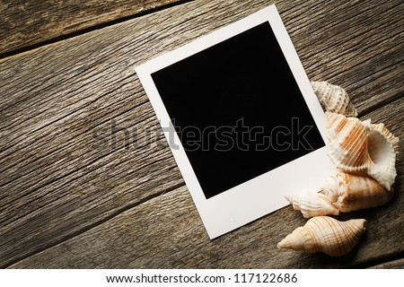 Instant photo frame on the wooden texture with seashells around - stock photo