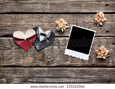 Instant photo frame with dried flowers and symbolic male and female heart shapes on old wooden background. - stock photo