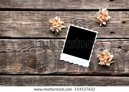 Instant photo frame with dried flowers on old wooden background. - stock photo