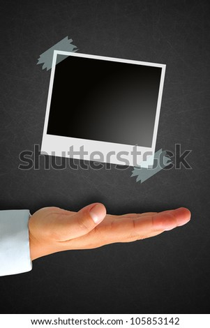 Instant photo on Blackboard with hand