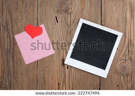 Instant photo with blank note and paper hearts on old wooden background - stock photo