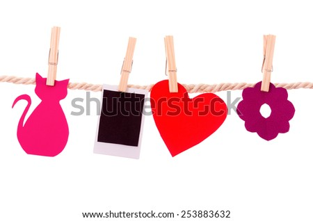 instant photograph and paper shapes hanging on a rope clothesline isolated on white - stock photo