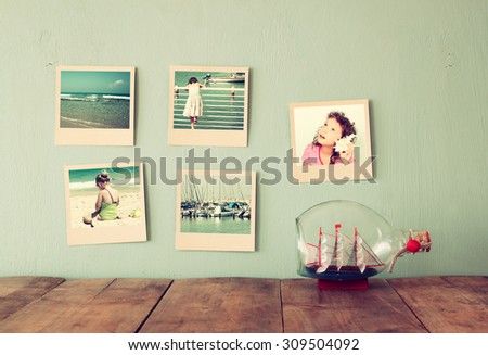 instant photos hang over wooden textured background next to decorative boat in the bottle. retro filtered image - stock photo