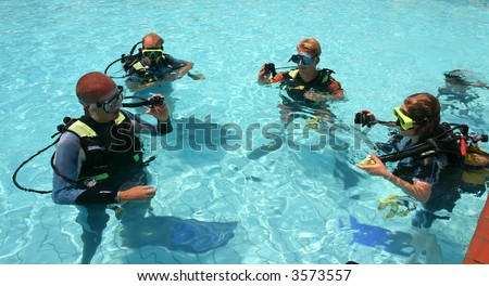 Instructor and students during scuba diving lessons - stock photo