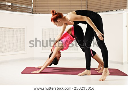 Instructor corrects head bending in downward face dog yoga pose - stock photo