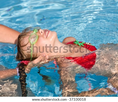 Instructor girl learn child swim in swimming pool.