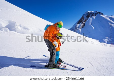 Instructor give ski lesson to little boy
