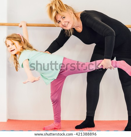 Instructor helping little girl on ballet barre - stock photo