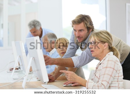 Instructor helping senior woman in computing class - stock photo